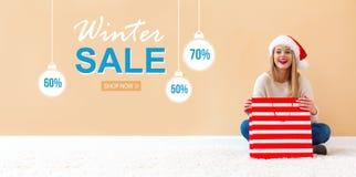Message de vente d'hiver avec la femme avec le chapeau de Santa tenant un sac à provisions photographie stock