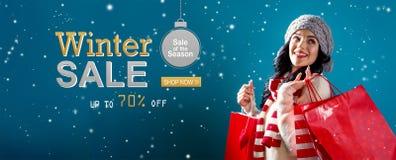 Message de vente d'hiver avec la femme tenant des sacs à provisions image stock