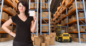 Message at distribution warehouse e. A woman holding a blank paper in a distribution warehouse, ideal for inserting your own message royalty free stock photo