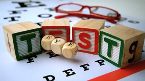 Message for eye test spelled out in dice and blocks on an eye test Royalty Free Stock Photo