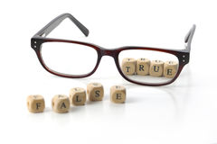 glasses and message - false true - in wooden letter blocks, isolated Royalty Free Stock Photography