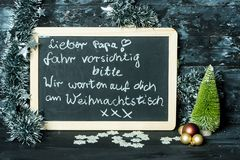 On a Christmas background a blackboard with a message from child to father: Drive carefully, we are waiting for you stock photos
