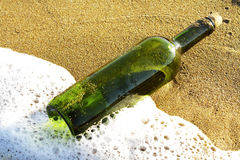 Message in a glass bottle in a beach. Message in a glass bottle in a solitary beach near the sea Stock Photography