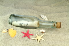 Message in a glass bottle. On beach sand Stock Photos