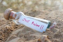 Message in glass bottle on brown  blurred bokeh background Royalty Free Stock Photography