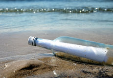 Message in a Glass Bottle on Sand Shore. A glass bottle has a message inside and it has washed up on a sandy ocean, lake shore. Use it to represent help Stock Photos