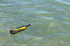 Message in glass bottle in the sea Stock Image