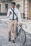 Message on a go. Confident young man in glasses using his smartphone and holding hand on his bicycle while standing outdoors Royalty Free Stock Photography