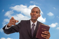 Message From Heaven. This is an image of man holding a bible against a cloud/sky background. This image can be used to represent Heavenly Message,sermon Stock Image