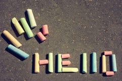 Message HELLO on asphalt children's crayons. Royalty Free Stock Image