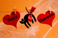 Message heureux de Halloween écrit à travers les coeurs rouges et le chat noir avec des chevilles pendant d'une ligne Image libre de droits