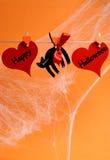Message heureux de Halloween écrit à travers les coeurs rouges et le chat noir avec des chevilles pendant d'une ligne - verticale  Photos libres de droits