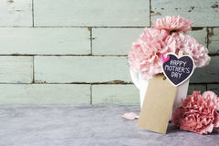 Message heureux de jour de mères sur le bois de coeur et le flowe rose d'oeillet Images libres de droits
