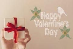 Message heureux de jour du ` s de Valentine avec le boîte-cadeau blanc avec la femme rouge de prise de ruban en main Photo libre de droits