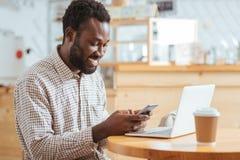 Message heureux de lecture d'homme au téléphone tout en se reposant en café Photo libre de droits