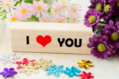 Message I love you spelled in wooden blocks with flower. Royalty Free Stock Image