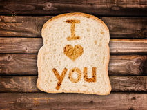 Message I love you written on a toasted slice of bread, on wooden planks Royalty Free Stock Photo