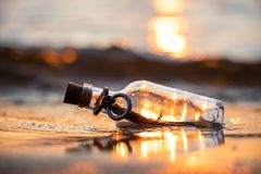 Free Message In The Bottle Against The Sun Setting Down Stock Image - 158565741