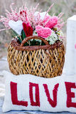 Message of love by needlework text. Message of love embroidered by needlework in red letters onto white material and behind a wicker basket with colored yarns stock photos