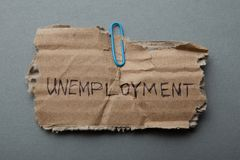 Message on the old torn cardboard: `Unemployment` on a gray background. stock images