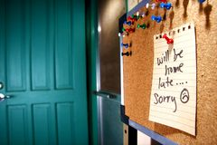 Message or reminder board with will be home late, sorry note Stock Images