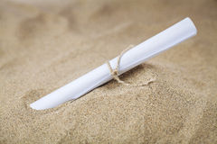 Message in the sand. Sheet of paper with message rolled in the sand royalty free stock image