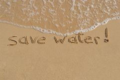 Message 'save water'. Demand to save water written in the wet sand at the beach. More then 97% of the water on the earth is saltwater and not usable as drinking Royalty Free Stock Images