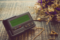 The message on the screen: Happy Valentine`s Day with fower on wooden background .  Old ancient pager style vintage Stock Photos