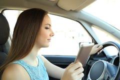 Message téléphonique distrait de lecture de conducteur conduisant une voiture photo stock