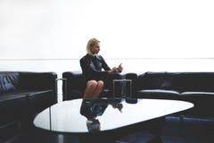 Message textuel à la mode de lecture de femme de son ami au téléphone portable pendant la pause dans l'intérieur de bureau, Photos stock
