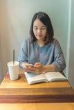 Message textuel asiatique d'étudiant avec des amis au téléphone intelligent Photographie stock libre de droits