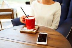 Message textuel de dactylographie de femme au téléphone intelligent dans un café Images stock