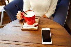 Message textuel de dactylographie de femme au téléphone intelligent dans un café Photographie stock
