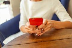 Message textuel de dactylographie de femme au téléphone intelligent dans un café Photo libre de droits