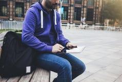 Message textuel de hippie sur la maquette de tablette ou d'écran vide de technologie Jeune homme de sourire avec le sac à dos uti photo libre de droits