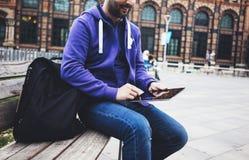 Message textuel de hippie sur la maquette de tablette ou d'?cran vide de technologie Utilisation de jeune homme de sourire num?ri photographie stock