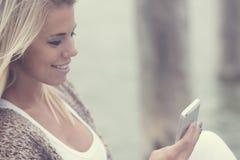 Message textuel de jeune fille de beauté au téléphone Image stock