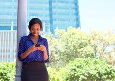 Message textuel de lecture de femme d'affaires au téléphone portable dehors images stock