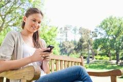 Message textuel de sourire de lecture de femme sur un banc de parc Images stock