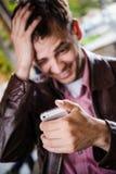 Message textuel de sourire dehors étonné et étonné de lecture d'homme au téléphone intelligent au café Foyer sélectif Image libre de droits