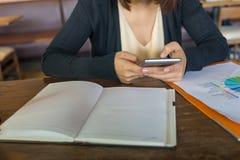 Message textuel et causerie de jeune femme sur le téléphone portable pendant le temps de travail photos libres de droits