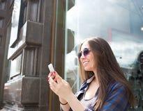 Message textuel gai de lecture de femme au téléphone de cellules Causerie femelle sur le téléphone portable photo stock
