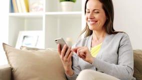 Message textuel heureux de femme sur le smartphone à la maison banque de vidéos