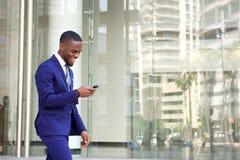 Message textuel heureux de lecture de jeune homme à son téléphone portable image libre de droits