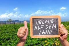 Message textuel - terre de DEM de forces d'appoint d'Urlaub sur un tableau noir d'ardoise photographie stock libre de droits