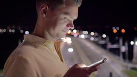 Message textuels caucasiens d'homme utilisant des applis au téléphone intelligent la nuit banque de vidéos