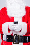 Message to elfs. Close-up of Santa Claus holding mobile phone while standing against grey background Stock Image
