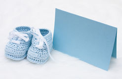 Message to the new baby. A pair of blue baby booties with a blank card on a white background, Message to the new baby stock photos