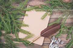 Message to Santa Claus. Christmas fir tree branches on wooden board with blank notebook and quill feather pen. Christmas or new ye Royalty Free Stock Images