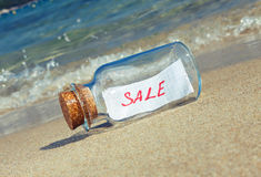 Message in a vintage bottle Sale on beach Royalty Free Stock Image